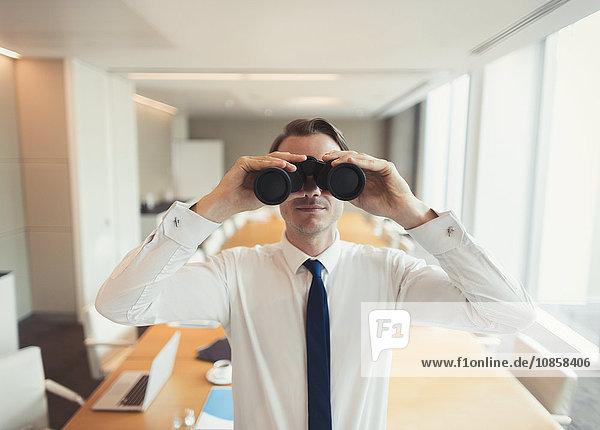 Portrait eines Geschäftsmannes mit Fernglas im Konferenzraum