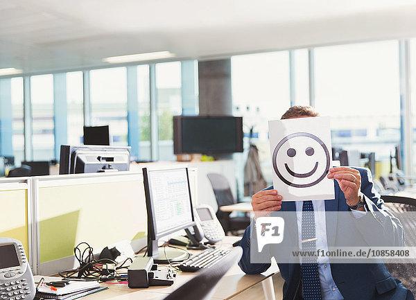 Porträt eines Geschäftsmannes mit Smiley-Gesichtsausdruck über seinem Gesicht im Büro
