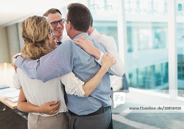 Lächelnde Geschäftsleute  die sich im Konferenzraum umarmen.