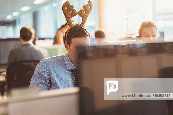 Geschäftsmann mit Geweih-Stirnband im Büro