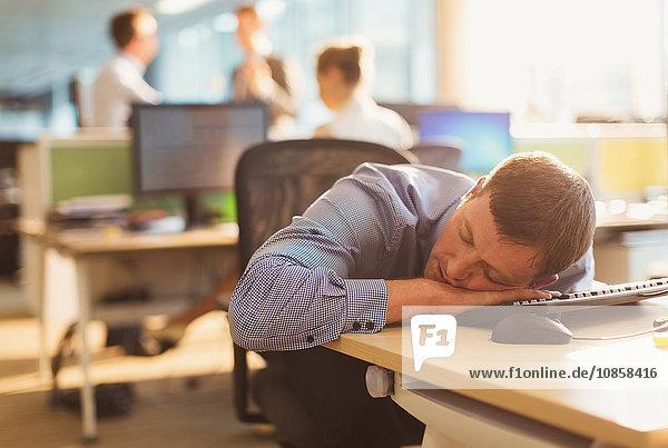 Geschäftsmann schläft auf dem Schreibtisch im Büro