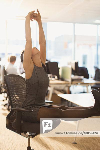 Geschäftsfrau streckt Arme über Kopf mit den Füßen auf dem Schreibtisch im Büro.