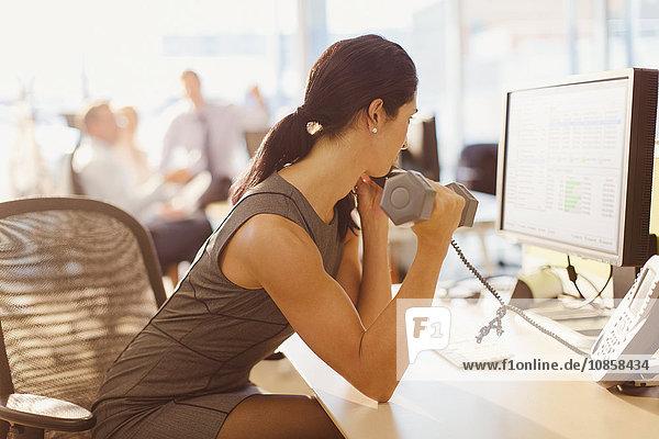 Geschäftsfrau macht Bizeps-Curls mit Kurzhantel und telefoniert am Computer im Büro.