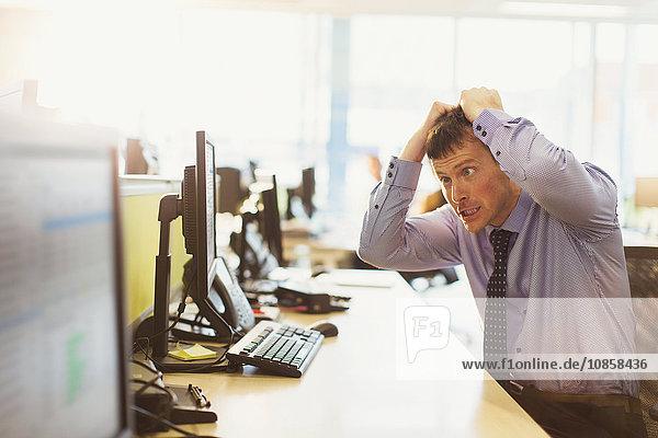 Gestresster Geschäftsmann  der sich am Computer im Büro die Haare auszieht.