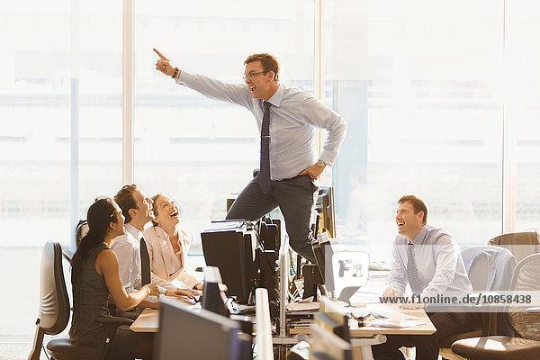 Lachende Kollegen  die übermütige Geschäftsleute auf Schreibtischen im Büro tanzen sehen.
