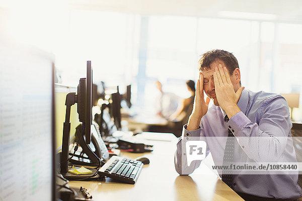 Gestresster Geschäftsmann mit Kopf in den Händen am Schreibtisch