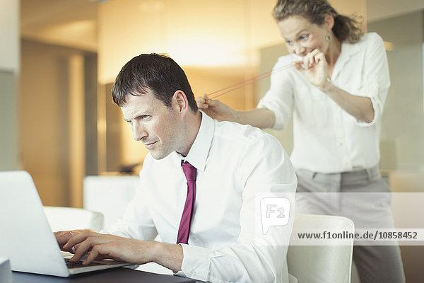Schelmische Geschäftsfrau zielt mit Gummiband auf ahnungslosen Geschäftsmann am Laptop