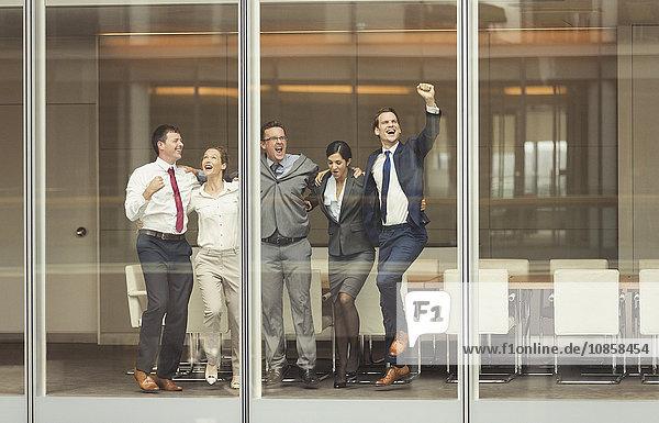 Geschäftsleute feiern und jubeln am Konferenzraumfenster