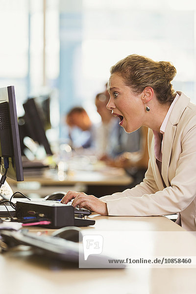 Schockierte Geschäftsfrau bei der Arbeit am Computer im Büro