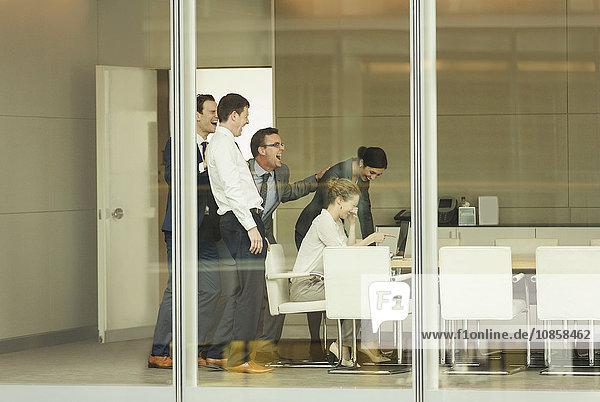 Geschäftsleute lachen über Laptop im Konferenzraum