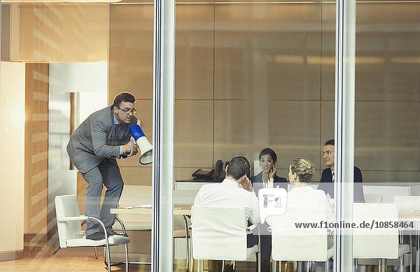 Geschäftsmann mit Megaphon auf dem Stuhl im Konferenzraum Meeting