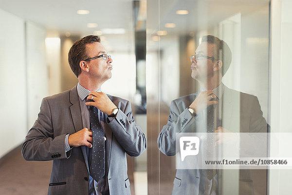 Spiegelung des selbstbewussten Geschäftsmannes bei der Anpassung der Krawatte im Büroflur