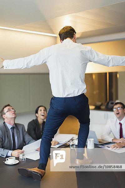 Überraschte Kollegen beobachten ausgelassene Geschäftsleute beim Tanzen auf dem Konferenztisch
