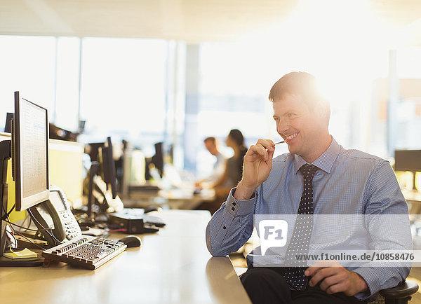 Lächelnder Geschäftsmann am Computer im sonnigen Büro