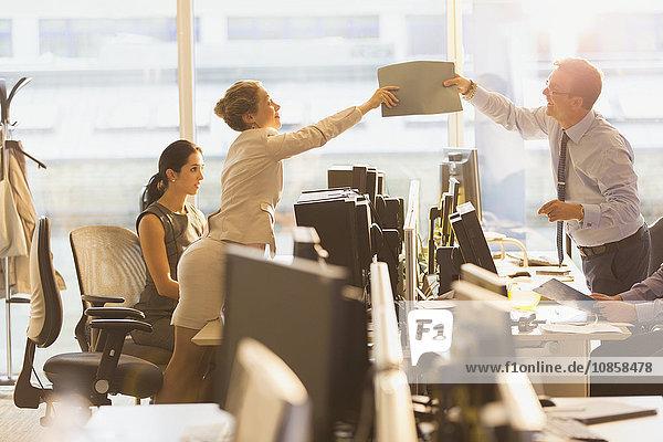 Geschäftsmann und Geschäftsfrau übergeben Ordner über Computer im Büro