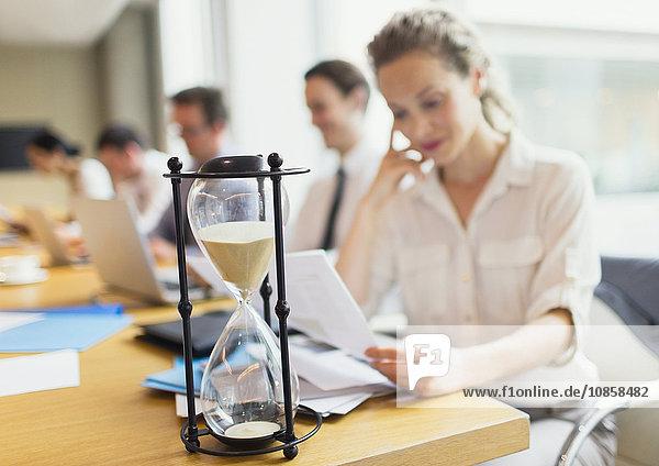 Sanduhr vor der Geschäftsfrau bei der Durchsicht der Unterlagen im Konferenzraum