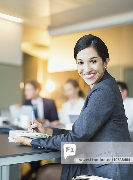Porträt einer lächelnden Geschäftsfrau  die sich Notizen im Konferenzraum macht.