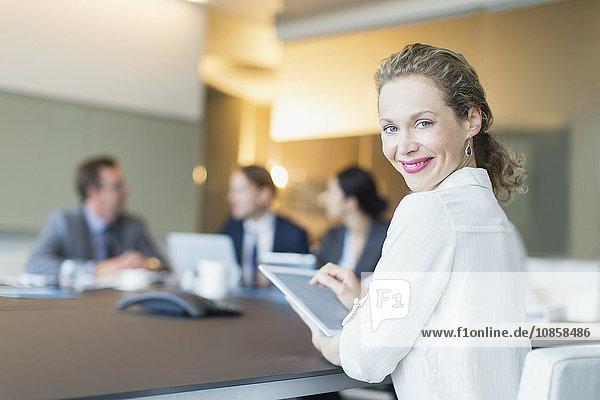 Portrait lächelnde Geschäftsfrau mit digitalem Tablett in Konferenzraumbesprechung