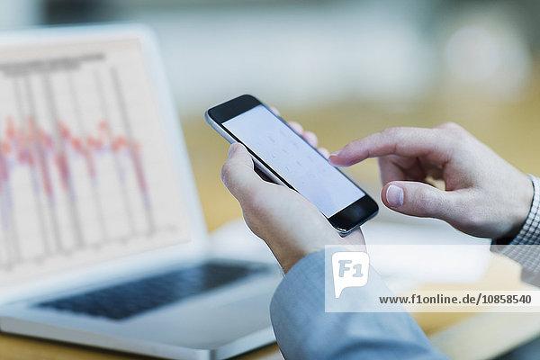 Nahaufnahme des Geschäftsmannes beim Wählen des Handys am Laptop