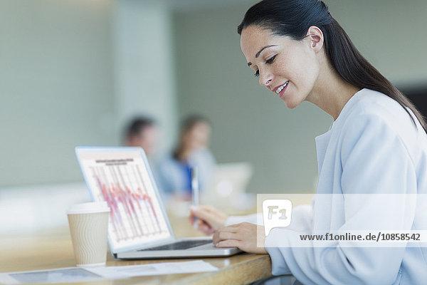 Lächelnde Geschäftsfrau bei der Arbeit am Laptop mit Kaffee im Konferenzraum