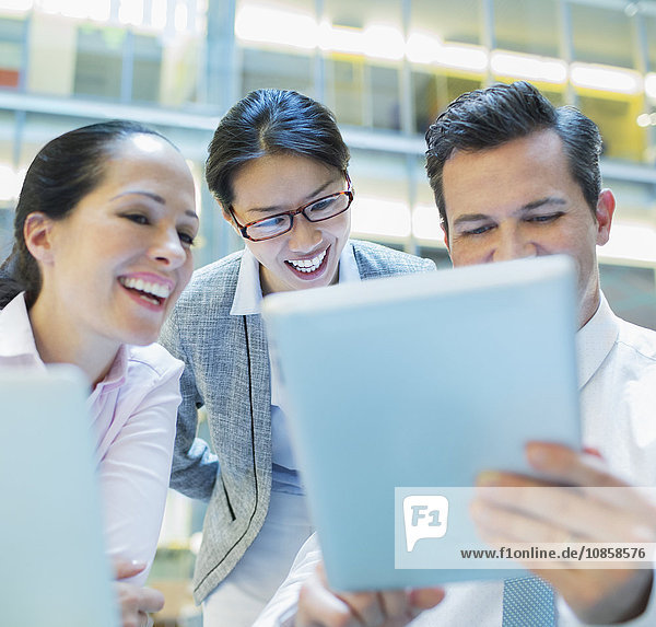 Smiling business people using digital tablet in office
