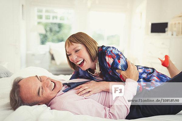 Gut gekleidetes reifes Paar  das im Bett lacht.