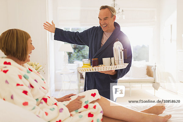 Enthusiastischer reifer Mann  der der Frau im Bett Frühstück serviert.