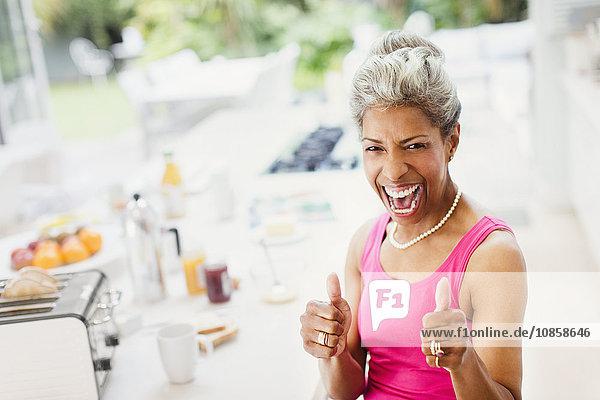 Porträt begeisterte  selbstbewusste  reife Frauen  die in der Küche die Daumen hochschlagen