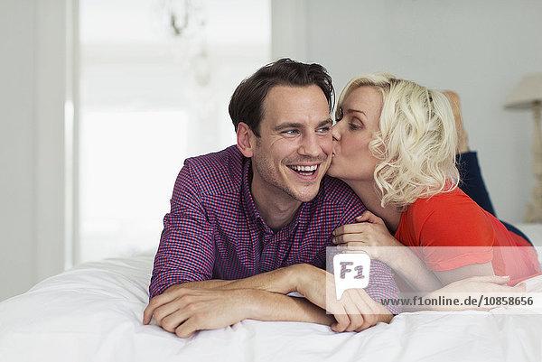 Zärtliche Frau küsst lächelnden Ehemann auf dem Bett