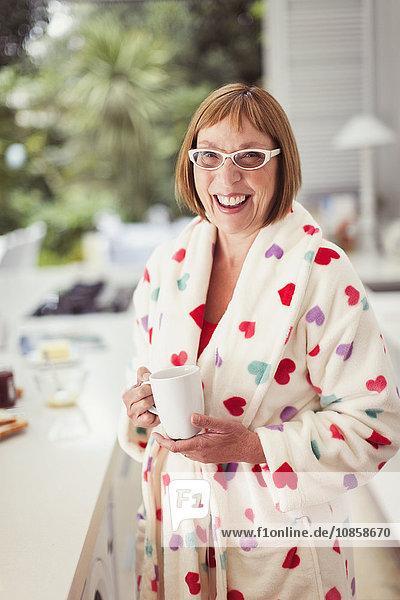 Portrait lächelnde reife Frau beim Kaffeetrinken im Bademantel