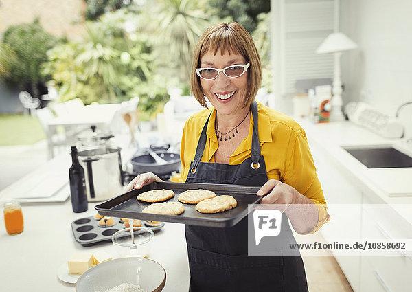 Portrait smiling mature woman baking cookies in kitchen