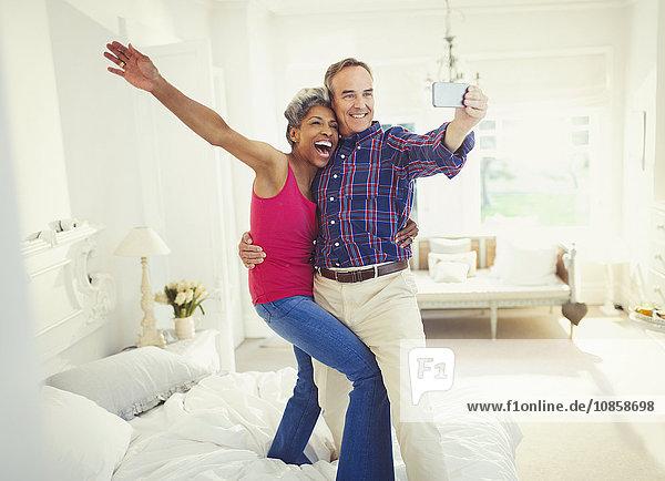 Verspieltes reifes Paar  das sich selbst auf dem Bett stehen lässt