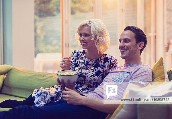 Paar sieht fern und isst Popcorn auf dem Wohnzimmersofa.