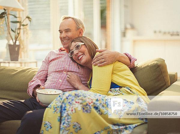 Liebevolles reifes Paar beim Fernsehen und Popcornessen auf dem Wohnzimmersofa