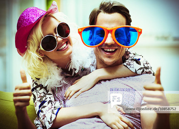 Portrait playful couple wearing costume sunglasses and hat gesturing thumbs-up