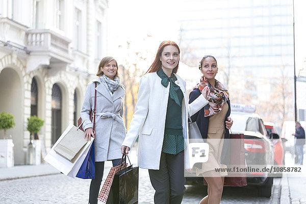Lächelnde Frauen mit Einkaufstüten überqueren die Stadtstraße