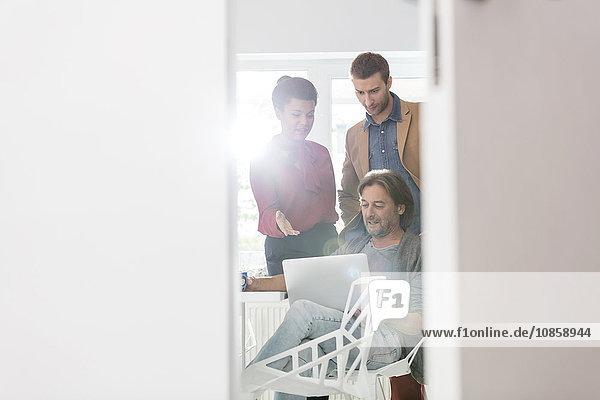 Kreative Geschäftsleute  die ihren Laptop im Büro teilen.