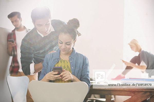 Junger Mann und Frau texten mit Handy im Büro
