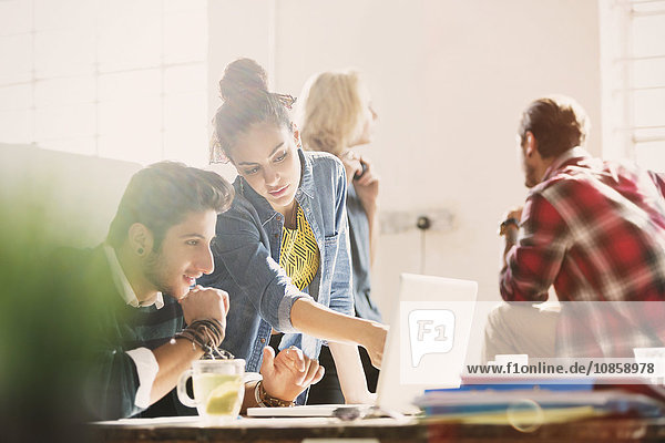 Kreative junge Geschäftsleute bei der Arbeit am Laptop im Büro