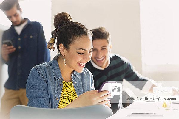 Lächelnde junge Geschäftsleute beim SMSen mit dem Handy