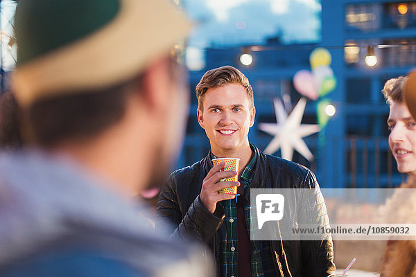 Young adult friends talking and drinking at nighttime rooftop party