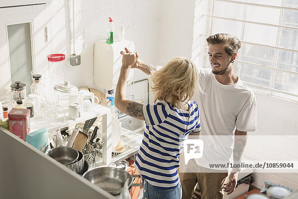 Young couple dancing in apartment kitchen