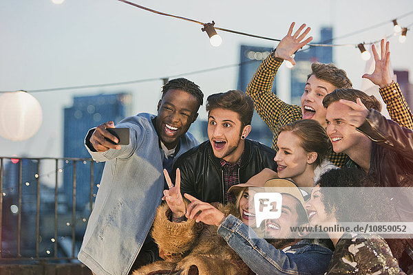 Enthusiastische junge erwachsene Freunde  die auf der Dachparty jubeln und sich selbst mitnehmen.