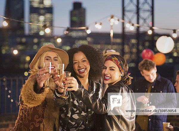 Portrait begeisterte junge erwachsene Freunde toasten Champagnerflöten bei nächtlicher Dachparty
