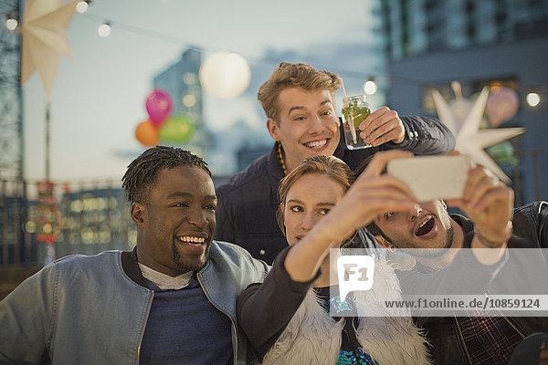 Junge erwachsene Freunde nehmen Selfie auf der Dachparty mit.