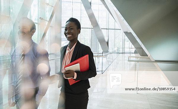 Lächelnde Geschäftsfrau in moderner Bürolobby