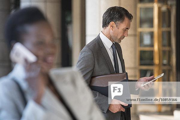 Corporate Geschäftsmann mit digitalen Tabletts im Freien
