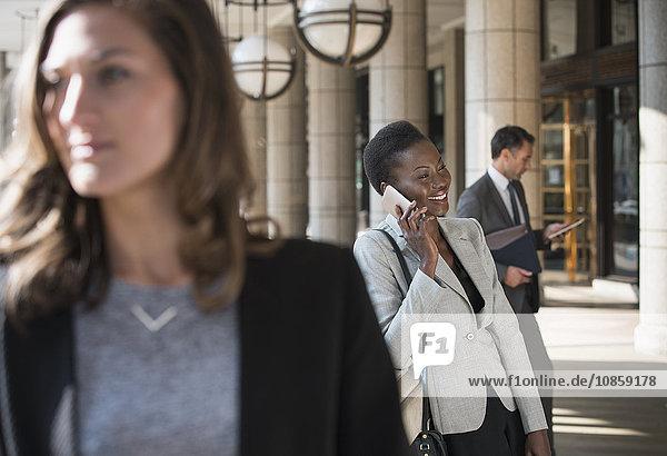 Lächelnde Geschäftsfrau im Gespräch auf dem Handy vor dem Gebäude
