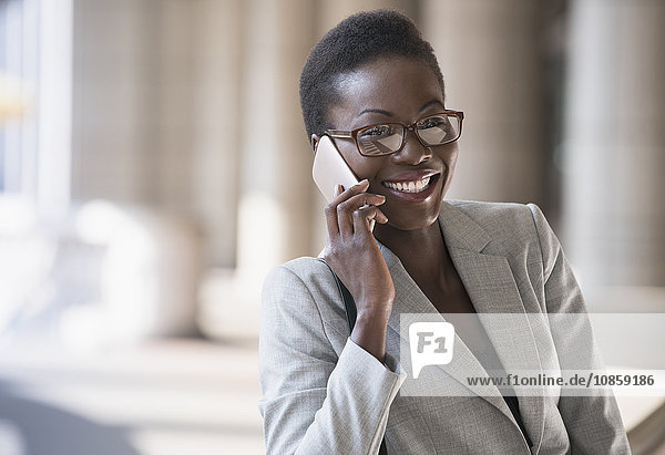 Smiling corporate businesswoman talking on cell phone