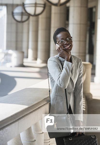 Portrait lächelnde Geschäftsfrau im Gespräch mit dem Handy